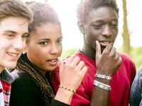 A closeup of three teenagers from the chest up, all looking in the same direction.