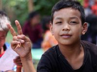 A closeup of a young boy giving the peace sign with his fingers.