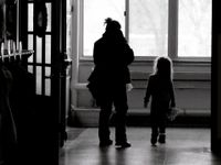 An adult woman and a young girl are walking down a school hallway.