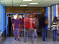 High school students are walking through one school hallway into another through opened double doors. The students are blurred as to imply fast movement and the passing of time.