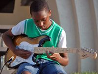 A young boy in jean shorts, a white t-shirt, and a green sweater vest is sitting outside in front of his school playing an electric guitar.