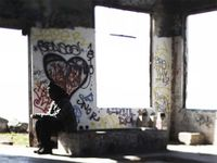 A man is sitting in an abandoned building with graffiti on the cement walls and benches.