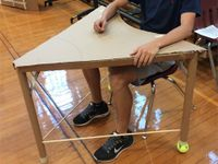 Chest down, a teen is sitting at a hand-made desk. It's made of a cardboard triangular desktop, three cardboard tubes as desk legs -- with tennis balls at the bottom of two of them -- and two solid, cylindrical wooden rods connecting the desk legs.
