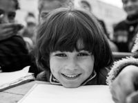 A closeup of a young kid's face, smiling, with their chin perched on their desk next to an open textbook.