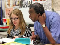 A male teacher is sitting next to a female student. The student is pointing to a page on an open textbook, talking. There is artwork on the wall behind them.