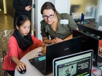 A female adult wearing a green shirt and glasses is sitting beside a young female student in a red blouse. They're both looking at a laptop computer.
