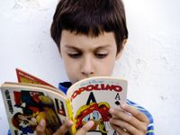A closeup of a young boy in a blue striped shirt against a white wall reading a book