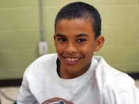 A closeup from the chest up of a young boy smiling directly at the camera. He's wearing a white t-shirt, and behind him is a green wall.