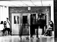 Three students are sitting on a large window sill on the left side of a high school hallway. Two students are sitting on a window sill on the right side of the school hallway. In the middle of the hallway is a faint, blurred image of three teenage student