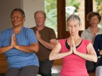 Adults sitting, kneeling on the floor practicing yoga