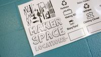 """A poster on a blue-painted brick wall that says, """"Maker Space Locations"""" on the left, and on the right of the poster it shows Monday through Friday and three maker spaces beneath each day, like """"ReMake,"""" """"Making 3D,"""" and StoryTeller."""""""