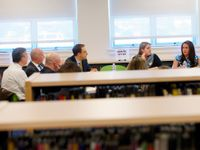 Nine adults are sitting around a table in a library, talking.