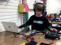 A young boy wearing a black, long-sleeve shirt and headphones has one arm extended next to his laptop, and the other hand is touching a remote control. In between his laptop and the remote control is a robotic device made out of plastic, metal, and wires.