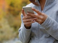 A closeup of a young woman's hands holding an iPhone. She's wearing a grey, full zip sweatshirt, and the autumn-colored background is blurred out.