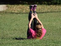 A teenage female in a pink t-shirt, black exercise pants, and purple tennis shoes is lying on the grass with her legs raised straight up and her hands reaching towards her feet.