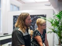 A side profile of a male and female adult from the waist up standing in a spacious white-walled room looking in the same direction. There's a black and white painting behind them, and a green, potted plant beside them.