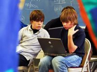 Two young teenage boys are sitting in foldable chairs in class. One has a laptop on his lap that they're both looking at.
