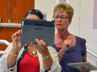 Two adult women are standing in a classroom with tablets in their hands. One of them is holding up their tablet, and both women are looking at it.