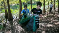 Middle schoolers help clear an area for an outdoor classroom