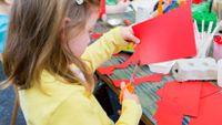 Kindergarten student cutting paper with scissors