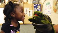 Photo of 4-year old and Twiggle the Turtle hand puppet