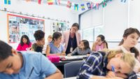 Teacher helping student in middle school classroom