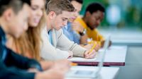 High school students take notes on paper and laptops in class