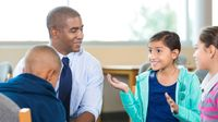 Teacher and students having a discussion in middle school