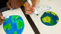 Two students draw the Earth with markers