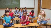 Elementary students meditating on desks in classroom