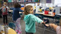 Students play a stretching game during a classroom break