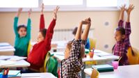 Elementary students stretching at their desks