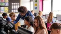 HIgh school teacher helping students working on computers.