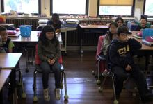 Primary students is sitting and smiling in the classroom.