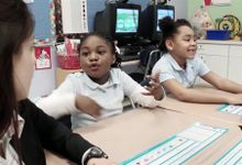 Students are talking to a teacher in a classroom