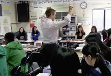 Teacher is teaching a group of senior students in a classroom.