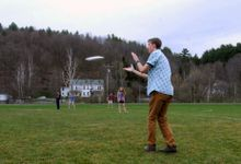 A group of students are hanging out and playing frisbee.