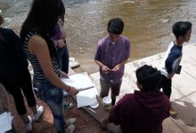 A group of students are working on their works and gather around the river