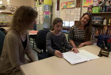 Two teachers are working with a student in a classroom