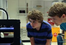 Two guy students is looking at their work.