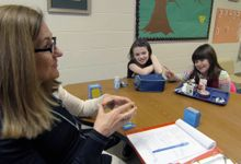 A teacher and students are working together in a working group setting.