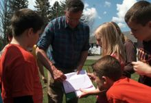 Students and teacher are working together in an outdoor setting.