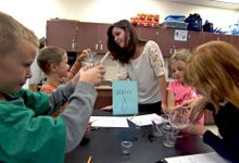Primary students are working in a science class with their teacher.