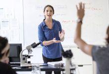 A teacher in a science classroom talks as a student raises their hand.