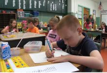 photo of a student writing at a desk