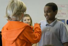 Two students fist bumping during circle practice at Valor Academy.