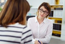 Female teacher engaged in discussion with a parent.