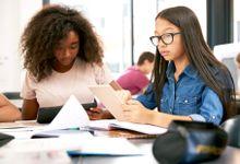 Two teenage schoolgirls using tablet computers in class.