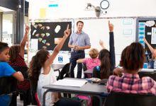 Kids raising hands in an elementary school class.