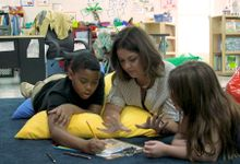 A teacher lying on the floor and helping two students with an assignment at Fall Hamilton Elementary School.
